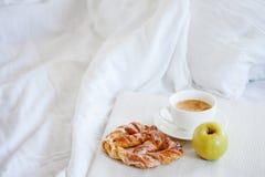 Δίσκος με το πρόγευμα σε ένα κρεβάτι Γλυκό pretzel, φλιτζάνι του καφέ και Apple Στοκ εικόνα με δικαίωμα ελεύθερης χρήσης