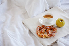 Δίσκος με το πρόγευμα σε ένα κρεβάτι Γλυκό pretzel, φλιτζάνι του καφέ και Apple Στοκ Εικόνες