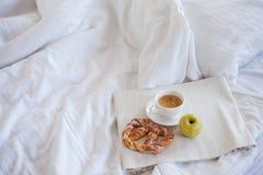 Δίσκος με το πρόγευμα σε ένα κρεβάτι Γλυκό pretzel, φλιτζάνι του καφέ και Apple Στοκ φωτογραφία με δικαίωμα ελεύθερης χρήσης