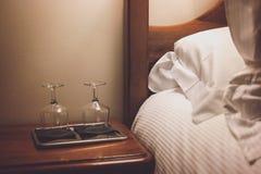 Δίσκος με wineglasses κοντά στο κρεβάτι Στοκ Φωτογραφία