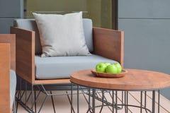 Δίσκος της Apple στον ξύλινο τοπ πίνακα δίπλα στο ξύλινο κάθισμα Στοκ Εικόνες