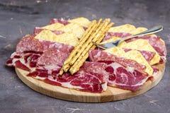 Δίσκος τροφίμων με τα εύγευστα κομμάτια σαλαμιού του τεμαχισμένου πιάτου ζαμπόν και κρέατος κροτίδων και ραβδιών ψωμιού Στοκ Εικόνες