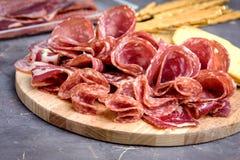 Δίσκος τροφίμων με τα εύγευστα κομμάτια σαλαμιού του τεμαχισμένου πιάτου ζαμπόν και κρέατος κροτίδων και ραβδιών ψωμιού Στοκ Φωτογραφίες