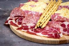 Δίσκος τροφίμων με τα εύγευστα κομμάτια σαλαμιού του τεμαχισμένου πιάτου ζαμπόν και κρέατος κροτίδων και ραβδιών ψωμιού Στοκ εικόνες με δικαίωμα ελεύθερης χρήσης