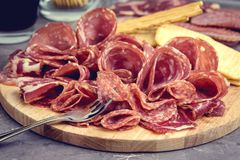 Δίσκος τροφίμων με τα εύγευστα κομμάτια σαλαμιού του τεμαχισμένου πιάτου ζαμπόν και κρέατος κροτίδων και ραβδιών ψωμιού που τονίζ Στοκ εικόνα με δικαίωμα ελεύθερης χρήσης