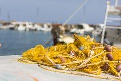 Δίχτυα του ψαρέματος και ελληνικά αλιευτικά σκάφη που δένουν στο λιμένα στην ανατολή στοκ φωτογραφίες με δικαίωμα ελεύθερης χρήσης