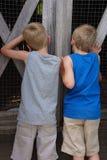 Δίδυμα αγόρια που κοιτάζουν αδιάκριτα μέσω του φράκτη παλαιό Barnyard στοκ εικόνες με δικαίωμα ελεύθερης χρήσης