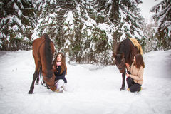 Δίδυμα αδελφές και άλογο στο χειμερινό δάσος στοκ εικόνες