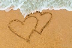 Δίδυμη διπλή καρδιά που επισύρεται την προσοχή στην αμμώδη παραλία με την προσέγγιση κυμάτων Στοκ Φωτογραφία