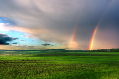 Δίδυμο ουράνιο τόξο με το συννεφιάζω ουρανό α Στοκ Εικόνες