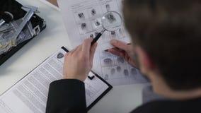 Δακτυλικά αποτυπώματα προσοχής ιδιωτικών αστυνομικών σε χαρτί, που χρησιμοποιεί την ενίσχυση - γυαλί, που λύνει τη δολοφονία φιλμ μικρού μήκους