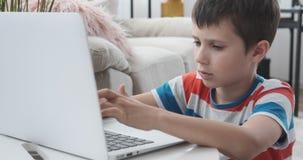 Δακτυλογράφηση αγοριών στο lap-top στο σπίτι απόθεμα βίντεο