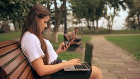 Δακτυλογράφηση γυναικών στο lap-top που μιλά τηλεφωνικώς απόθεμα βίντεο
