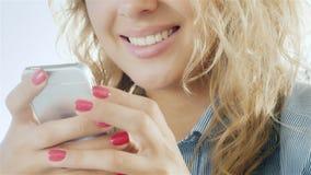 Δακτυλογράφηση γυναικών στο smartphone και χαμόγελο Η κινηματογράφηση σε πρώτο πλάνο παραδίδει το πλαίσιο μπορεί να δει με ένα τη απόθεμα βίντεο