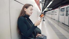 Δακτυλογράφηση γυναικών στο smartphone στο σταθμό μετρό Αναμονή το τραίνο φιλμ μικρού μήκους