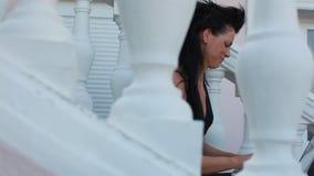 Δακτυλογράφηση γυναικών στη σκάλα πίνοντας το κρασί απόθεμα βίντεο