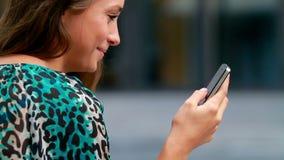 Δακτυλογράφηση κοριτσιών σε έναν κινητό. απόθεμα βίντεο