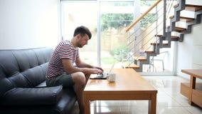 Δακτυλογράφηση νεαρών άνδρων στο lap-top στο σπίτι απόθεμα βίντεο