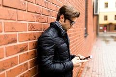 Δακτυλογράφηση της πλάγιας όψης μηνυμάτων κειμένου του όμορφου νεαρού άνδρα στην έξυπνη περιστασιακή ένδυση που κρατά το κινητό τ Στοκ φωτογραφίες με δικαίωμα ελεύθερης χρήσης