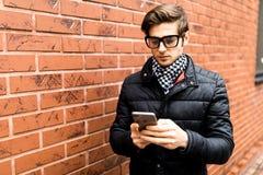 Δακτυλογράφηση της πλάγιας όψης μηνυμάτων κειμένου του όμορφου νεαρού άνδρα στην έξυπνη περιστασιακή ένδυση που κρατά το κινητό τ Στοκ Φωτογραφία