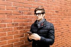 Δακτυλογράφηση της πλάγιας όψης μηνυμάτων κειμένου του όμορφου νεαρού άνδρα στην έξυπνη περιστασιακή ένδυση που κρατά το κινητό τ Στοκ εικόνες με δικαίωμα ελεύθερης χρήσης