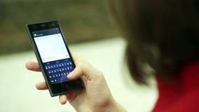 Δακτυλογραφώντας γυναίκα σε μια κινηματογράφηση σε πρώτο πλάνο συσκευών smartphone απόθεμα βίντεο