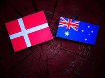 Δανική σημαία με την αυστραλιανή σημαία σε ένα κολόβωμα δέντρων που απομονώνεται Στοκ Φωτογραφίες