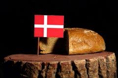 Δανική σημαία σε ένα κολόβωμα με το ψωμί στοκ εικόνες