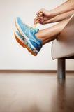 Δαντέλλα δρομέων τα παπούτσια τρεξίματός της που κάθονται στο κρεβάτι στοκ φωτογραφίες