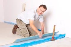 δαπέδωση εγκαθιστώντας τον τοποθετημένο σε στρώματα εργαζόμενο Στοκ Φωτογραφία