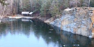 Δασική λίμνη με την παγωμένη επιφάνεια με τα δύσκολα βουνά και τα ξύλινα σπίτια Βαθιά δασική άποψη η ανασκόπηση εύκολη επιμελείτα Στοκ φωτογραφία με δικαίωμα ελεύθερης χρήσης