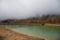 Δασική λίμνη με τη γέφυρα κατά τη διάρκεια της ηλιόλουστης ημέρας με τα χειμερινά δέντρα και τον μπλε νεφελώδη ουρανό Όμορφη φυσι Στοκ Εικόνες