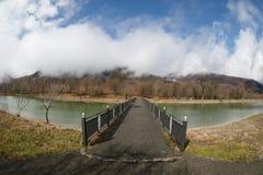 Δασική λίμνη με τη γέφυρα κατά τη διάρκεια της ηλιόλουστης ημέρας με τα χειμερινά δέντρα και τον μπλε νεφελώδη ουρανό Όμορφη φυσι Στοκ φωτογραφία με δικαίωμα ελεύθερης χρήσης