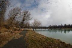 Δασική λίμνη με τη γέφυρα κατά τη διάρκεια της ηλιόλουστης ημέρας με τα χειμερινά δέντρα και τον μπλε νεφελώδη ουρανό Όμορφη φυσι Στοκ εικόνα με δικαίωμα ελεύθερης χρήσης
