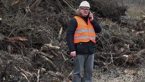 Δασικός επιθεωρητής που μιλά στο smartphone πλησίον πριονισμένους στους σωρός Μπους και τις πιέσεις φιλμ μικρού μήκους