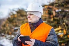 Δασικός μηχανικός με το PC ταμπλετών κοντά στους σωρούς των κούτσουρων Στοκ φωτογραφία με δικαίωμα ελεύθερης χρήσης