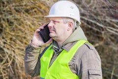 Δασικός μηχανικός που μιλά στο τηλέφωνο κυττάρων κοντά στο σωρό των κλαδίσκων Στοκ φωτογραφία με δικαίωμα ελεύθερης χρήσης