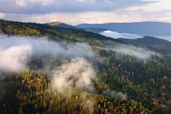 Δασικό τοπίο φθινοπώρου βουνών κατά τη διάρκεια του ομιχλώδους ηλιοβασιλέματος στοκ εικόνα