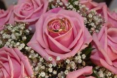 Δαχτυλίδια γαμήλιου γάμου και ανθοδέσμη των ρόδινων τριαντάφυλλων Στοκ Φωτογραφίες