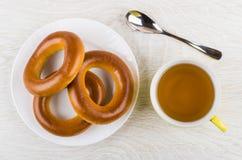 Δαχτυλίδια ψωμιού στο πιάτο, το φλυτζάνι του τσαγιού και το κουταλάκι του γλυκού Στοκ Εικόνες