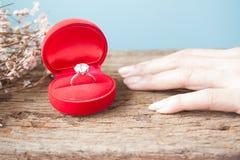 Δαχτυλίδι διαμαντιών στο κόκκινο κιβώτιο με το χέρι γυναικών στον ξύλινο πίνακα, Engagem Στοκ φωτογραφία με δικαίωμα ελεύθερης χρήσης