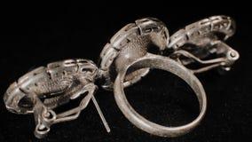 Δαχτυλίδι και δύο σκουλαρίκια σε μια μαύρη περιστρεφόμενη στάση Κοσμήματα ασφαλίστρου Μακροεντολή απόθεμα βίντεο