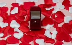 Δαχτυλίδι σε ένα κόκκινο κιβώτιο σε ένα υπόβαθρο των καρδιών κόκκινος και άσπρος Γαμήλιο δαχτυλίδι στο κιβώτιο στοκ εικόνες