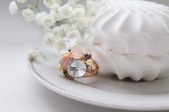 Δαχτυλίδι αγαλμάτων με marshmallows και τα λουλούδια σε μια ελευθερία saucerof Στοκ Εικόνες