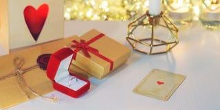 Δαχτυλίδι αρραβώνων που περιβάλλεται από το δώρο, κεριά, κάρτα παιχνιδιού καρδιών Στοκ Εικόνες