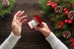 Δαχτυλίδι αρραβώνων στα θηλυκά χέρια μεταξύ των διακοσμήσεων Χριστουγέννων στο ξύλινο υπόβαθρο Στοκ Εικόνες