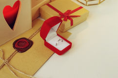 Δαχτυλίδι διαμαντιών δέσμευσης σε ένα κόκκινο κιβώτιο βελούδου Φάκελος με τη σφραγίδα κεριών που περιβάλλεται από τα δώρα Στοκ Φωτογραφία