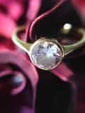 Δαχτυλίδι διαμαντιών στο κόκκινο ροδαλό υπόβαθρο Στοκ Φωτογραφίες
