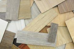 Δείγματα του φυλλόμορφου και βινυλίου κεραμιδιού πατωμάτων σε ξύλινο Backgroun στοκ εικόνες