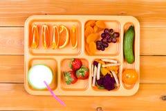 Δειγματοληπτική συσκευή φρούτων στο δίσκο μεσημεριανού γεύματος με το γάλα Στοκ Φωτογραφία